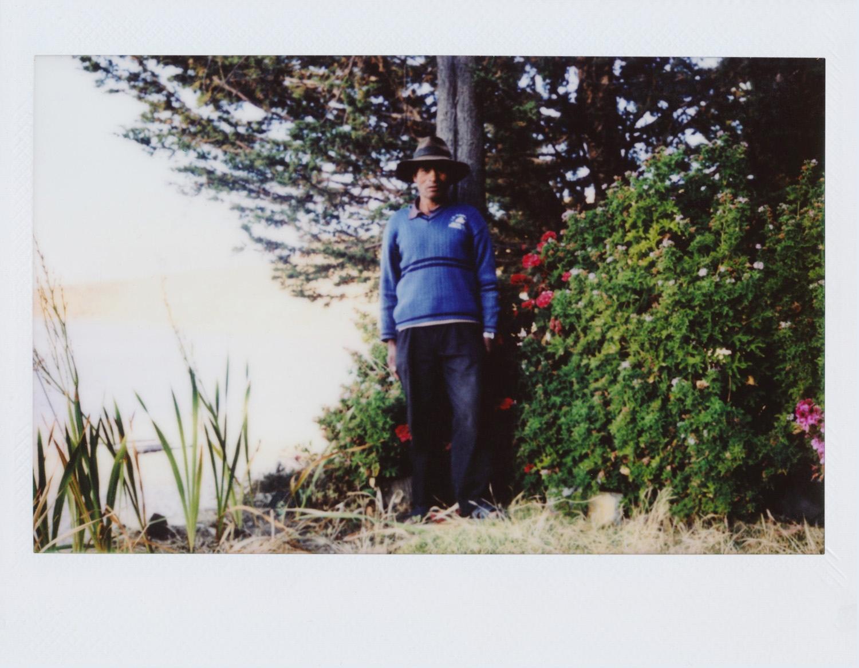 Antonio Ticona / PAISAJES Tengo 57 años. He nacido en Ch'allapampa. Trabajo en agricultura, albañilería, la boletería, la pesca, también manejo la lancha en la comunidad... La Isla del Sol es un lugar bonito con paisajes, aire libre, no como la ciudad. Lo que más me gusta es la tranquilidad, no hay mucho movimiento de turismo aquí en el centro de la isla. Mi trabajo es sobre el paisaje de la isla como los cerros, donde se caen los burros, el Illampu… Mi foto favorita es la del Illampu porque salió bonito y se ve el lago. Nunca había hecho fotos antes, la primera vez es esta. Me gusta mucho lo de hacer fotos y aprender. Me ha gustado mucho la experiencia de las fotos porque es la primera vez que hacemos algo así en la isla. Salir en conjunto al cerro explicar lo nuestro, en Santa Bárbara sacar los cerros de la comunidad. Elegí un cerro donde salimos a hacer nuestros rituales, a pedir por la lluvia... Voy a seguir haciendo fotos sobre todo de paisaje y algunos personajes. He aprendido a sacar fotos, a encuadrar. Me gustó mucho montar la exposición en conjunto nos ayudamos entre nosotros. Lo que me hace feliz es lo que vivo aquí, tranquilo.