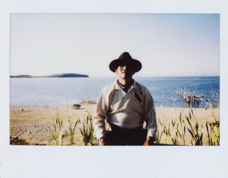 Eusebio Mendoza / ACHACHILAS (Altas montañas temerosas con poderes de nuestros ancestros) Tengo 52 años y nací en la Isla del Sol. Me dedico a la agricultura y a la pesca. La Isla del Sol para mi significa un templo sagrado. Desde nuestros ancestros la Isla del Sol siempre ha sido una isla sagrada. Lo que más me gusta de vivir aquí es que es una isla muy tranquila, llena de aire puro, aquí la gente somos muy amables, nos comprendemos entre los comunarios, los vecinos que vivimos aquí. Somos casi 270 afiliados en la comunidad, vivimos en común, en conjunto. Mi trabajo: A mí lo que me gusta es andar en las montañas, por eso el título habla de las montañas sagradas. Yo ando con el sueño. Si me hace llamar algún cerro, a mediodía o a media mañana, si me llama antes de que salga el sol voy. Si no llego, los Achachilas me castigan y tengo que seguir con el sueño de la noche. Yo ando con el sueño... Mi foto favorita es la de la montaña más alta el Puskallavi. Tiene mucho poder, en las mañanas su magnetismo es muy fuerte, es como un padre para nosotros. Con el montaje de la exposición de las fotos me quedé muy sorprendido, ver cual puede ir primero, cual abajo, de acuerdo a las montañas. Es la primera vez que he cogido una cámara y me gusta, es lindo sacar fotos de nuestros paisajes, hermanos, cerros, nuestras montañas, lugares arqueológicos. Me ha gustado mucho la experiencia porque aprendí como hacer una foto limpia, sin fallos, el encuadre, los planos...aprendí mucho con este taller. Lo que más me gustó fue salida fotográfica a Santa Bárbara, un lugar sagrado, ahí están los aguayos de nuestras abuelitas donde vamos a hacer rituales. Ese día en la mañana es lindo sacar las fotos cuando no hay demasiada luz. Desde esa montaña se ve casi toda la Isla del Sol. Yo me llevo de estos talleres un gran recuerdo de compartir con mis hermanos que hemos trabajado en equipo y las hermanas que nunca han agarrado una cámara. La experiencia de las señoras seguro que de aquí en adelante 