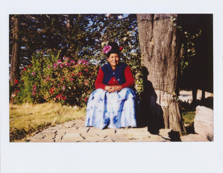 Juana Arias / MI COMUNIDAD, DONDE CRECÍ Me llamo Juana y tengo 63 años. He nacido en la comunidad de Ch´alla en la Isla del Sol. He vivido siempre aquí. Me dedico a los cultivos, sembradíos, la chakra, sembramos oka, papa, haba, papalisa y cebada. La Isla es para mí muy sagrada, como de chiquita nací y ningún lugar es como aquí. Es una isla que no tiene contaminación, vivimos al aire libre. Me gusta de vivir aquí estar con mi familia, cuando estoy aquí reunida con mis hijos, almorzamos en grupito, con Nelson, esa es mi alegría: mis hijos. Mi trabajo es mi caminar por las montañas, me encanta el camino donde nací, ese lugar me encanta. Llegar arriba. Lo que más me gusta es esa montañita, todas las fotos que saqué fue por ahí donde yo crecí, allí iba de niña a pastear ovejas. Mi foto favorita es ahí dónde está el burrito Pepe en la montaña. Nunca había hecho fotos antes y les agradezco a ustedes porque me encanta tomar fotos: subir a las montañas. Me siento feliz con la cámara, como veo, como saco. Voy a seguir haciendo fotos, cuando vuelvan tal vez fotos de extraños les van a esperar. Yo les agradezco mucho por haber venido aquí, nosotros que no teníamos nada de cámaras, claro que los celulares sacan, pero les agradezco por enseñarme. Lo que más me ha gustado de la experiencia es compartir en grupo, esa es alegría para mí, hablarnos, como hacemos. He aprendido mucho, subir a la salida en Santa Bárbara a los Achachilas. Seguiré haciendo fotos hasta donde pueda. Me hace feliz vivir en esta isla, me encanta porque no hay como esta comunidad, el sol, el clima, aquí me siento sana. Cuando voy a La Paz me enferma, aquí estoy con mis amigas compartimos, alegre.