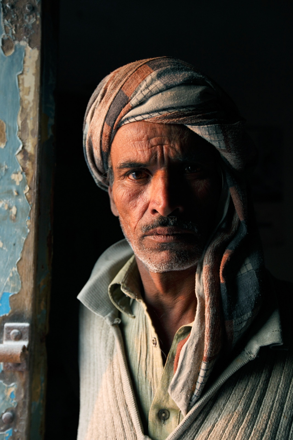 A salt carver stands in the doorway of his workshop at the distribution area of the Khewra Salt mine.