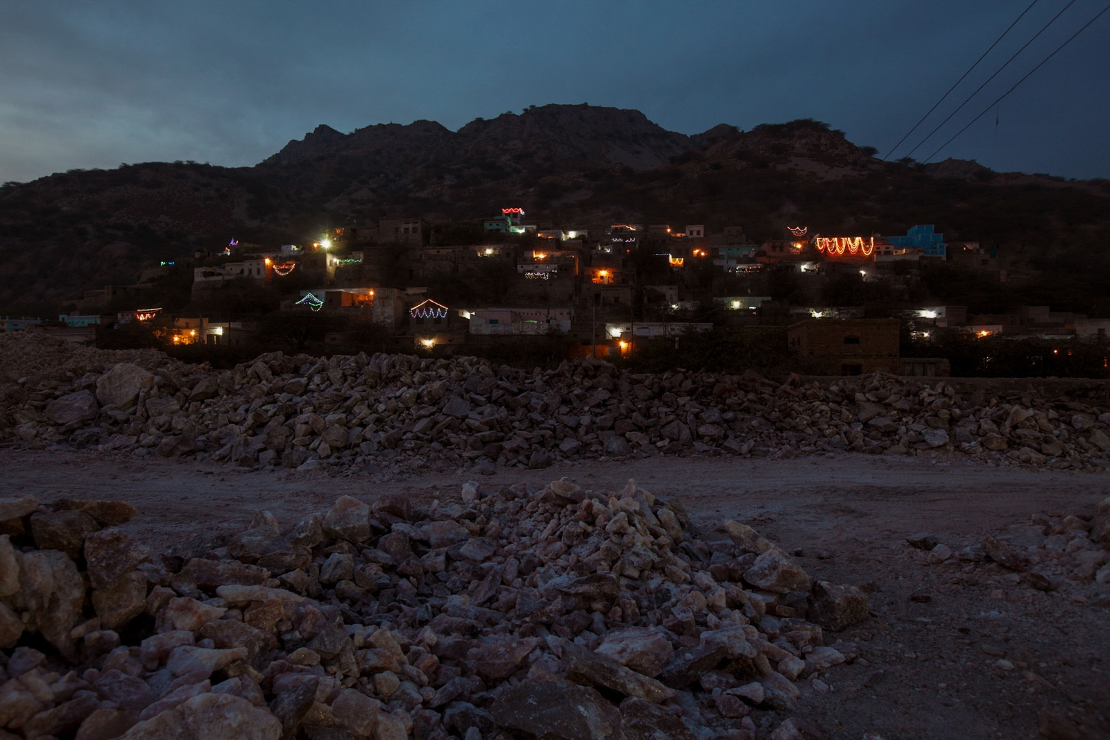 Salt miners houses are illuminated on the hillside above the Warcha salt mines below them.
