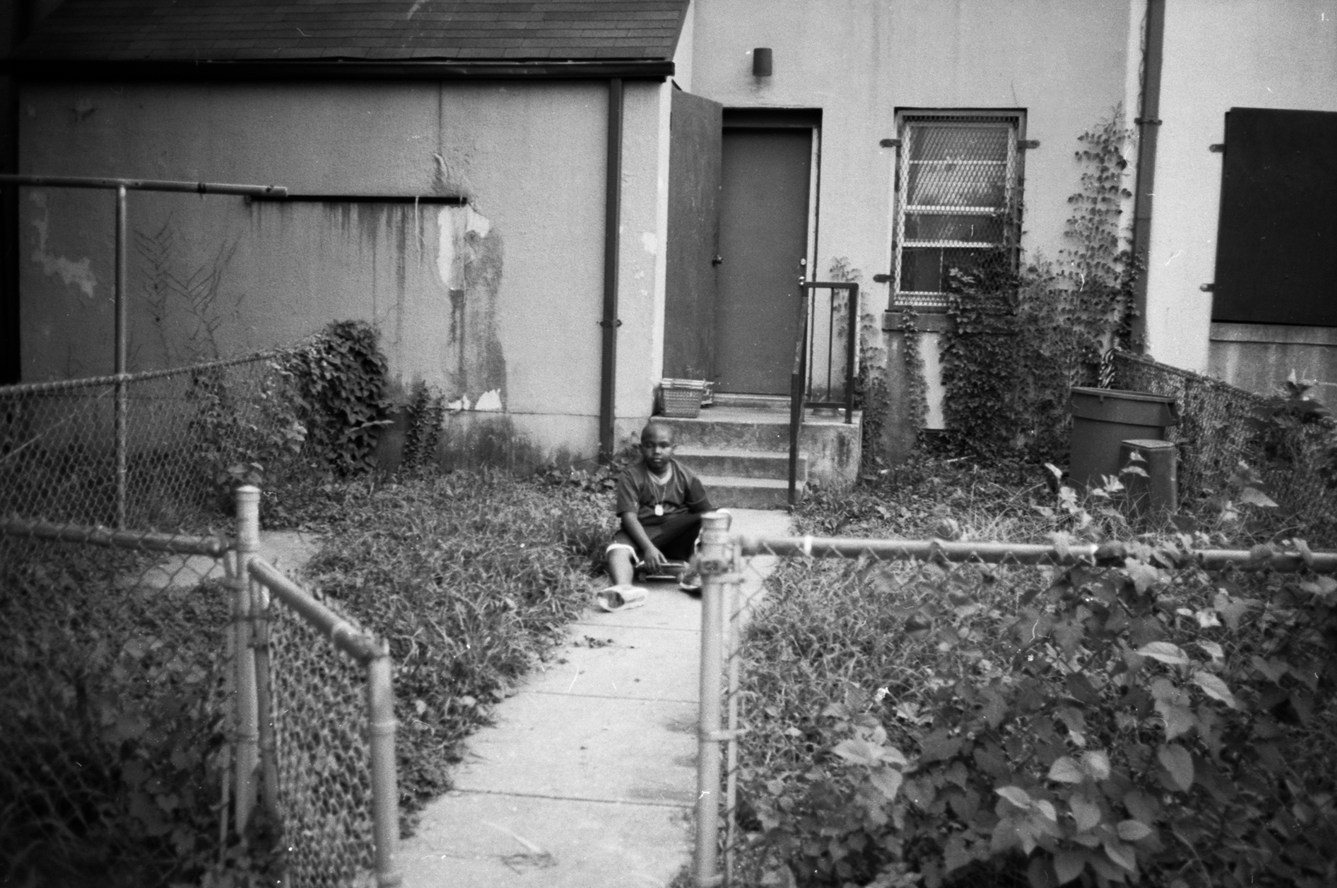 """Zion Archer sits on a skateboard in his backyard in Barry Farm August 2017. """"Barry Farm is not really a good place because they really shoot up a lot, they do bad things, and people rob people's stuff, like they took my scooter. That's why I don't like Barry Farms. The only thing I like is when I play with my friends,"""" says Archer."""