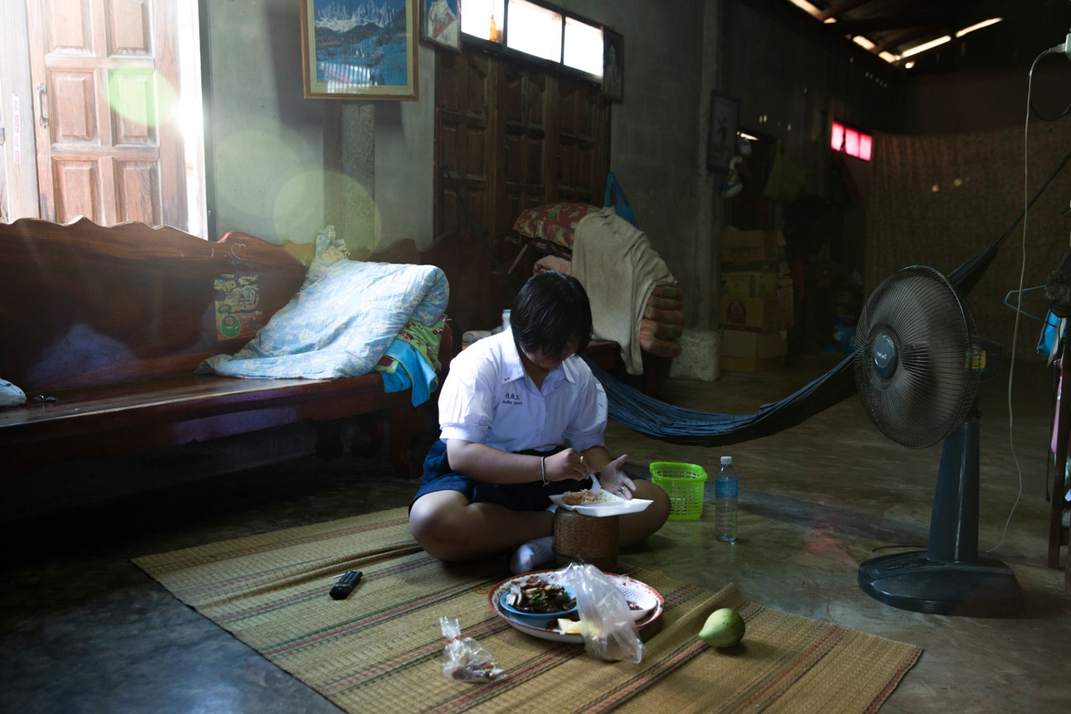 High-school student Wanpen Khunna, 17, sits in her house eating breakfast before school. When she was 15 she was sued by the mining company for narrating a Thai television documentary on the plight of the villages. The TV station was also sued.