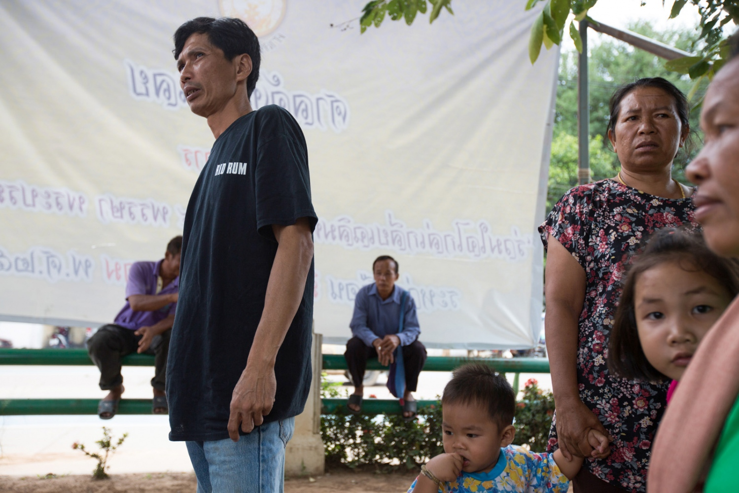 Surapan Rujichaiyavat and other core-members of Ban Rak Khon Kerd wait outside the Loei District Court in support of a fellow villager who was sued by the mining company.
