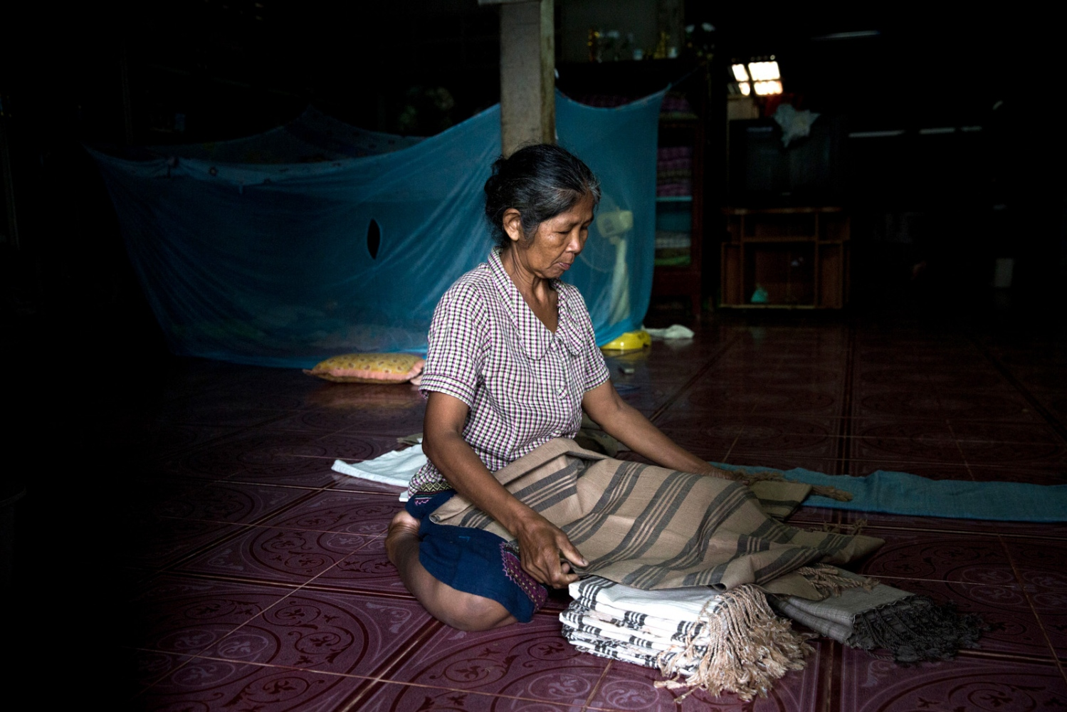 Ranong Kongsaen, a core-member of the Khon Rak Ban Kerd conservation group folds cloth that she weaved herself for extra income in the doorway of her house.