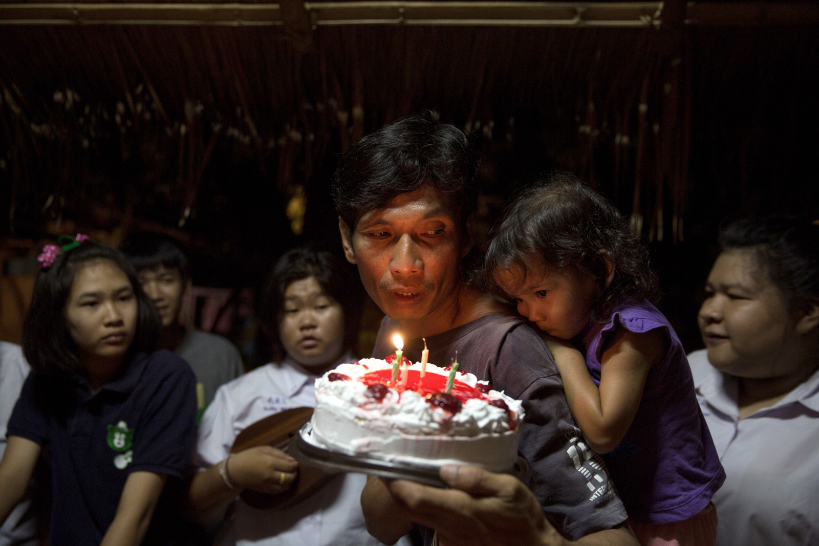 Por Mai holds a cake for his daughters birthday during a family celebration in Na Nong Bong village.