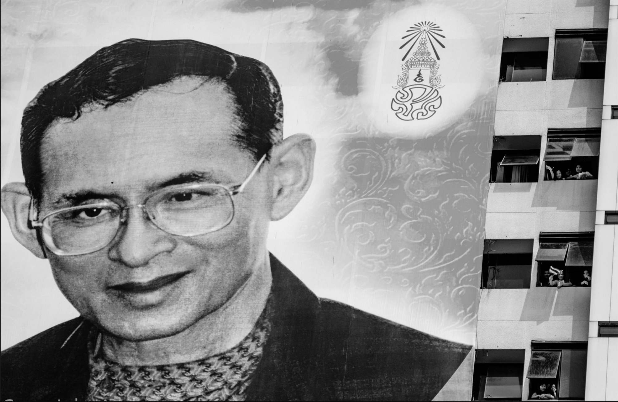 A large poster depicting the King Bhumibol Adulyadej of Thailand hanging outside of the Ministry of Environment building in Bangkok as workers wave to anti-government demonstrators during a period a massive protest against Prime Minister Yingluck Shinawatra.
