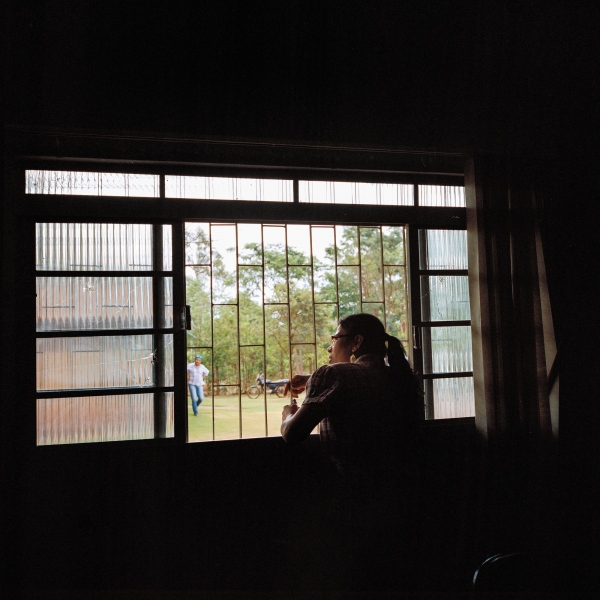 November 28, 2016. Local psychologist Elizeti Moreira looks out the window of health center in the Dourados Guarani-Kaiówa Reservation in Matto Grosso Du Sul, Brazil. Oliveira committed suicide the previous week and had come to see her for help beforehand, he had spoken about his inability to get work and support his four children, although he had never mentioned thoughts of suicide. He was 39 years old.
