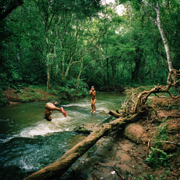November 30, 2016.  Tamil Flores, 9, left, and her brother Hudson Flores, 6, play in a stream in an occupied village of Guaiuiry near Amambai Indigenous Reserve in Matto Grosso Du Sul, Brazil. The land which is owned by a farmer has been occupied by a group of Kaiowa Indigenous people. The farm owner killed the Chief of the community, Nizio Gomes, with hired security forces a year ago. The community has not had a single suicide. and they attribute that to their practice of cultural customs to ward off bed sprits.