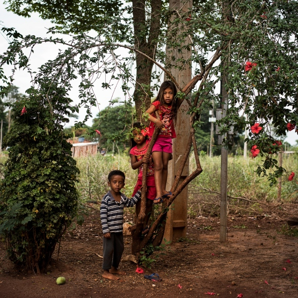 November 28, 2016. Siblings, Miguel Desilva, 4, Bruna Feliciano Desilva, 6, and Neto De Silva, 8, pose for a photo un the village of Jiguarapiru in the Dourados Guarani-Kaiówa Reservation in Matto Grosso Du Sul, Brazil.