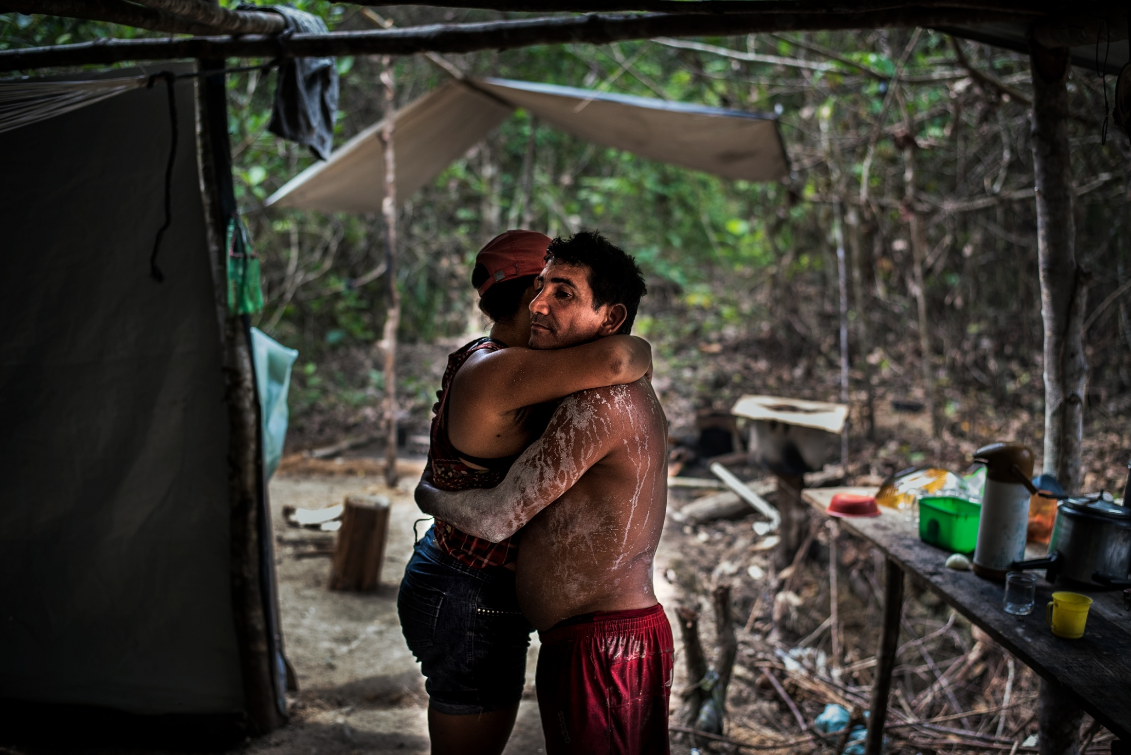 A garimpeiro   or illegal gold miner hugs his wife as he's apprehended by the ICMBio government agents