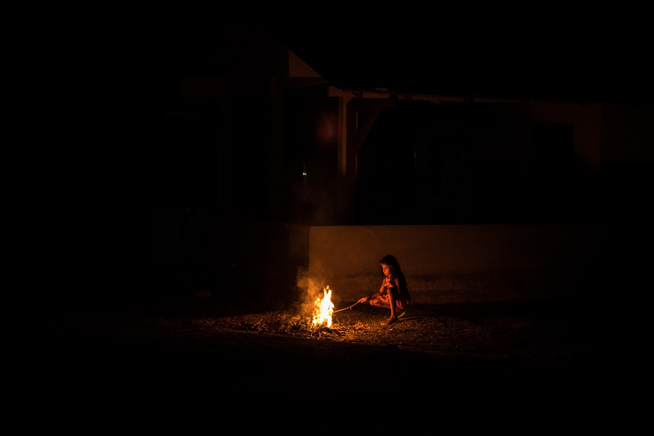 A Munduruku girl sits by a fire in the village of Praia do Mangue outside Itaituba, Para state, Brazil.