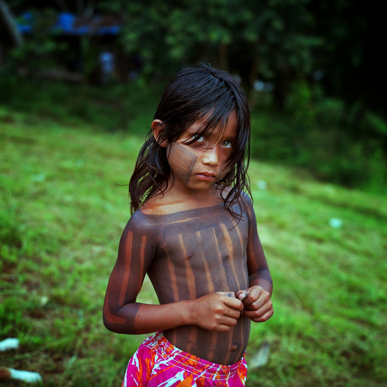 "2014. A child from the Xikrin village of ""Pot crô"" stands for a photo on the banks of the Rio Bacaja, the rivers name meaning ""the water that runs in river is the same as the blood that flows through our veins."" The Xikrin are a warrior tribe that have strongly resisted the Belo Monte Dam. Their villages were divided and leadership weakened after Norte Enegria, the company building the dam, enacted the Emergency Plan. The Emergency Plan gave each indigenous village 30,000 Brazilian Reais or 10,000 American Dollars per month from 2011-2013, driving them to split up for more money. Many of the chiefs supported the plan buying boats, motors, and televisions, while others tried to maintain a resistance to the Dam. The program was devastating to the regions indigenous tribes, impacting their health and culture. Communities stopped farming their land and began depending on modern food, paid for with free money, and people who had always lived a subsistence lifestyle fell into dependance on those from the outside."