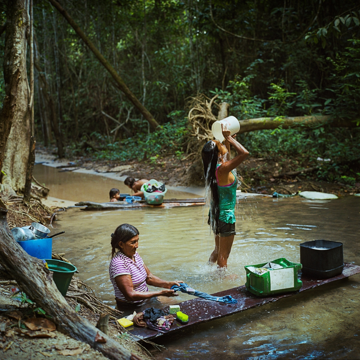 2014.  Munduruku women bathe and do laundry in a creek by the village of Sawre Muybu. Their land was recently demarcated by the Bazilian government after years of fighting for recognition of their territory on the Tapjos River once known as Mundurukânia. The demarcation led to the cacelling of government plans to construct a MegaDam that would have flooded much of their traditional lands in Para State, Brazil. 40 other dams are still planned and being built on the Tapajos River Basin impacting sacred sites and the rivers health. The dams are part of Brazil's Growth Acceleration Programme (PAC), which also includes a rapid expansion of soy production and mining in the gold rich region.  /Aaron Vincent Elkaim