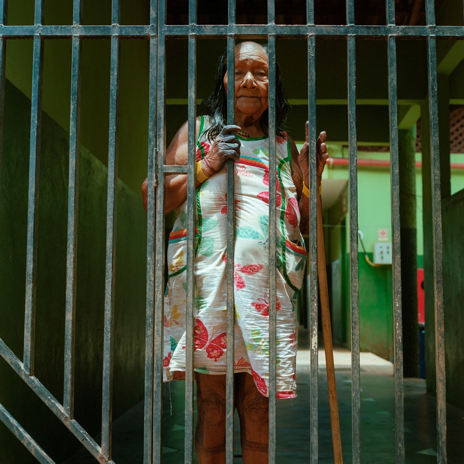 2016. Maria, a Xikrin Kayapo woman, stands in the gate of the Casa do Indios, a place where indigenous people can stay while visiting the city of Altamira. The Xikrin live along the Bacaja river, a tributary of the Xingu that has been severely impacted by the Belo Monte Dam. Illegal gold mining has also become an large problem on the upper Bacaja because of the lower water levels since the dams completion.  /Aaron Vincent Elkaim
