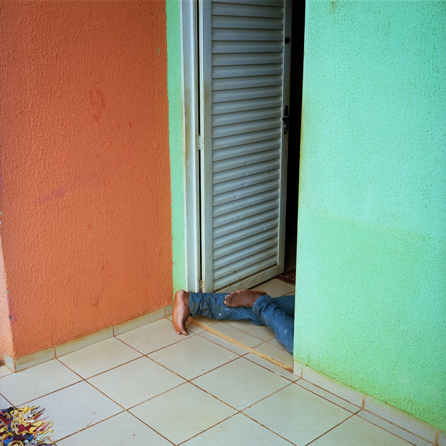2016. A man sleeps in his doorway in the resettlment community of Jatoba. There are five communities such as this one around Altamira, each with identical housing build by Norte Energia. People who once lived on the rivers as fisherman have been relocated here where there is little employment, and the neighbours are strangers. Crime, violence and alcholism have become major problems in the communities.