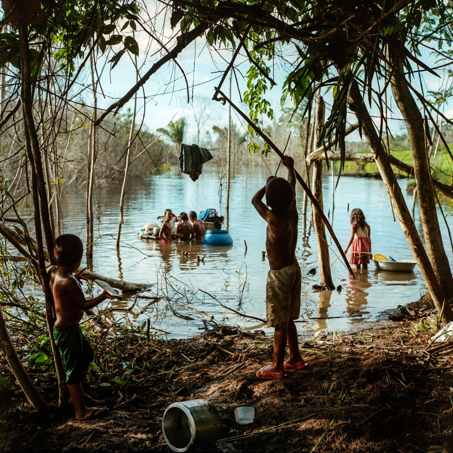 2017. Riberino Children play by the water at a relocation site on the Belo Monte Dam Reservoir.  Riverine families that were displaced from their flooded land have recenlty been returning to life on the water yet face new challenges as the river ecosystem has been transformed.