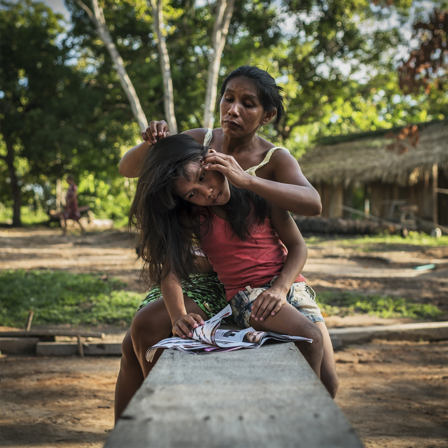 2016. A Munduruku mother checks her daughters hair for insects in the village of Praia Do Mangue near the city of Itaituba in Para state, Brazil.