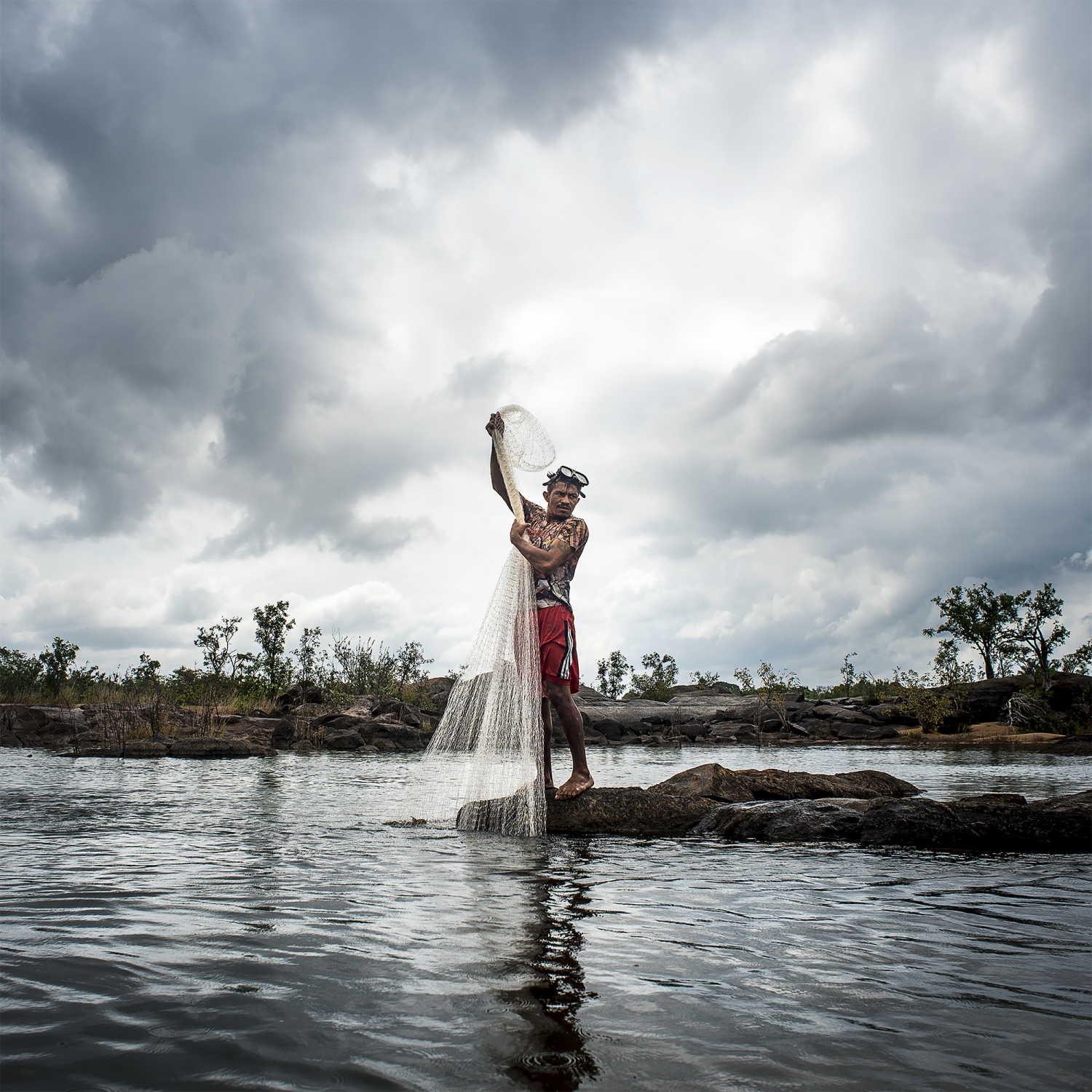 2016. Caboco Juruna from the Juruna village of Miratu in the Paquiçamba Indigenous Reserve on the Volta Grande do Xingu, fishes for Acarí fish on the Xingu River. This part of the Xingu River has had it's water flow blocked by the newly completed Belo Monte Dam, severly damaging the fishing livelihoods of the people. The Juruna are now worried that the construction of the upstream Belo Sun Gold Mine, which will be the largest open pit gold mine in Brazil, will further damage their river and way of life. Aaron Vincent Elkaim