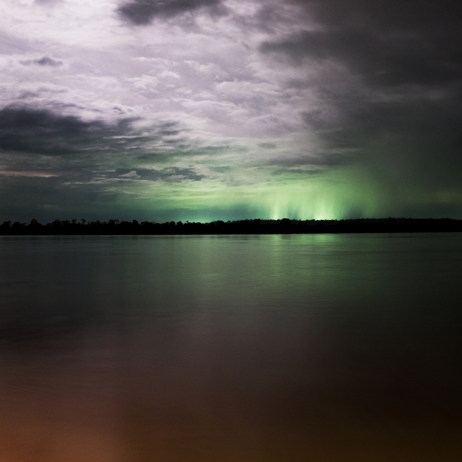 2014. The construction site of the Belo Monte Dam lights up the sky over the Xingu River, seen from the nearby city of Altamira. During it's construction it was the largest infrastructure project in South America.  /Aaron Vincent Elkaim