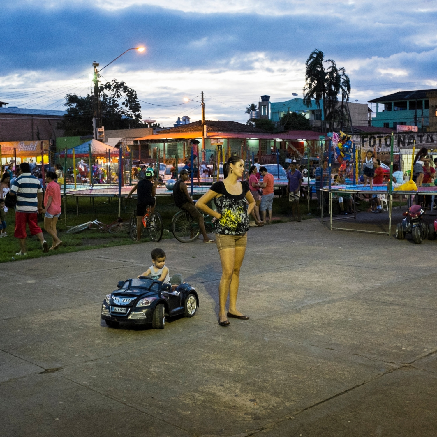During the heart of construction for the Belo Monte Dam, the city of Altamira was a boomtown. Each weekend along the riverfront people would gather, the restaurants and bars would be packed, and entertainers would perform. Here on an evening in March 2014, a child drives an electric miniature car while her mother watches a performance in the square. Now that construction has been completed, the riverfront is empty most nights.  /Aaron Vincent Elkaim
