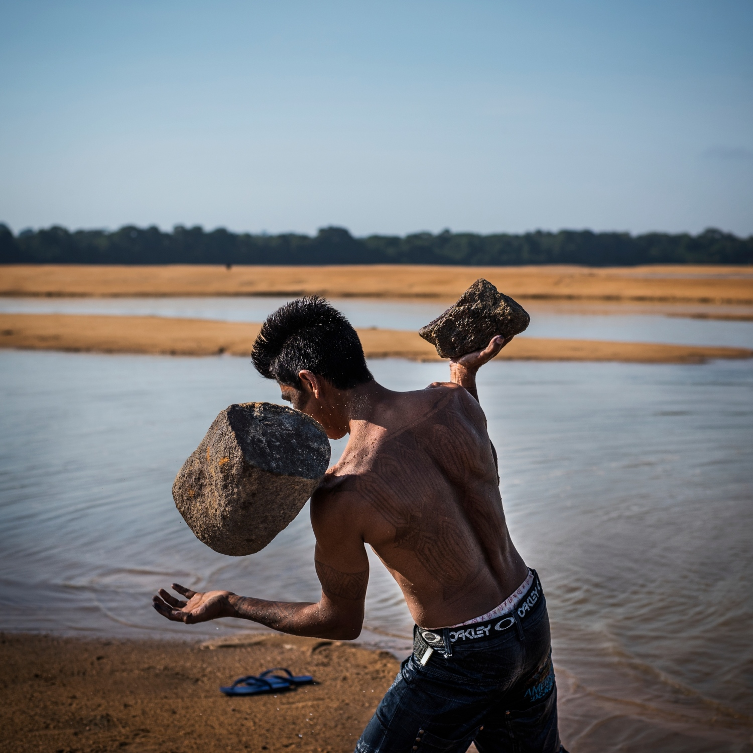 November 26, 2014. A member of the Munduruku indigenous tribe carries rocks on a sandbar on the Tapajos River in protest against plans to construct a series of hydroelectric dams in in Para State, Brazil. The tribe members used the rocks to write 'Tapajos Livre' (Free Tapajos) in a large message in the sand in an action in coordination with Greenpeace. After years of fighting, the Munduruku were successful in lobbying the government to offically recognize their traiditonal territory with a demarcation. This recognition forced IBAMA, Brazil's Environmental Agency, to cancel the environmental licensing process for the 12,000 megawatt Tapajós hydroelectric complex, due to the unconstitutional flooding of their now recognized land. But the fight continues as 40 more dams are still planned for the river basin.  /Aaron Vincent Elkaim