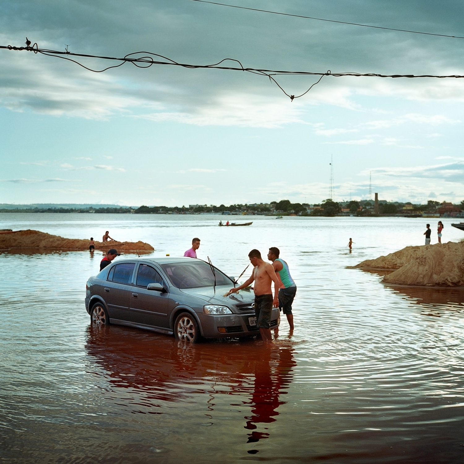 2014. Men wash their car in the high waters of the Xingu River in the city of Altamira, Brazil. Money and people poured into the city with the arrival of thousands of workers to build the Belo Monte Dam. The population exploded and the economy boomed, but today with the completion of the major construction, the people and money are leaving and economic hardship is settling in. /Aaron Vincent Elkaim