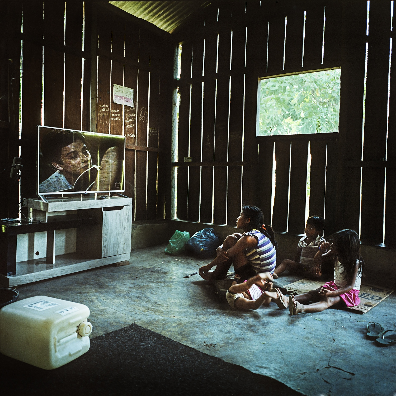 2014.  A Munduruku family watch Brazilian telenovelas  in the village of Sawre Muybu. Although living self sufficiently off the land their villages have generators, fridges and televisions. Some indigenous communities are provided with these goods by government and industry hoping to win their support for the proposed development projects.  /Aaron Vincent Elkaim