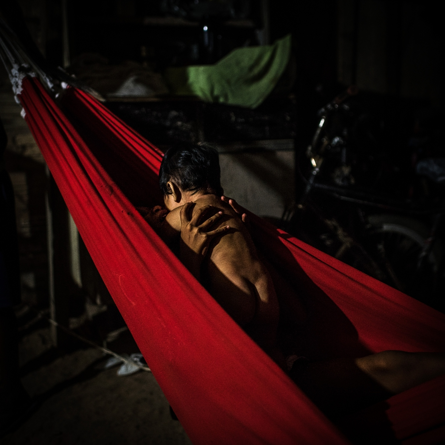 2016. A Munduruku girl holds her baby brother in a hammock in the village of Praia Do Mangue near the city of Itaituba in Para state, Brazil. The Munduruku are currently fighting against government plans to build 40 dams on the Tapajos River impacting traditional lands and destroying sacred sites.  /Aaron Vincent Elkaim