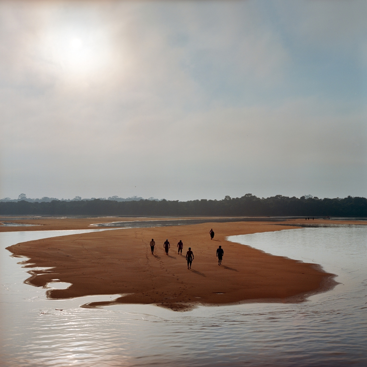 November 26, 2014. Members of the Munduruku indigenous tribe walk on a sandbar on the Tapajos River as they prepare for a protest against plans to construct a series of hydroelectric dams on their river in in Para State, Brazil. The tribe members used the rocks to write 'Tapajos Livre' (Free Tapajos) in a large message in the sand in an action in coordination with Greenpeace. After years of fighting, the Munduruku were successful in lobbying the government to offically recognize their traiditonal territory with a demarcation. This recognition forced IBAMA, Brazil's Environmental Agency, to suspend the environmental licensing process for the 12,000 megawatt Tapajós hydroelectric complex, due to the unconstitutional flooding of their now recognized land. But the fight continues as 40 more dams are still planned for the river basin.  /Aaron Vincent Elkaim