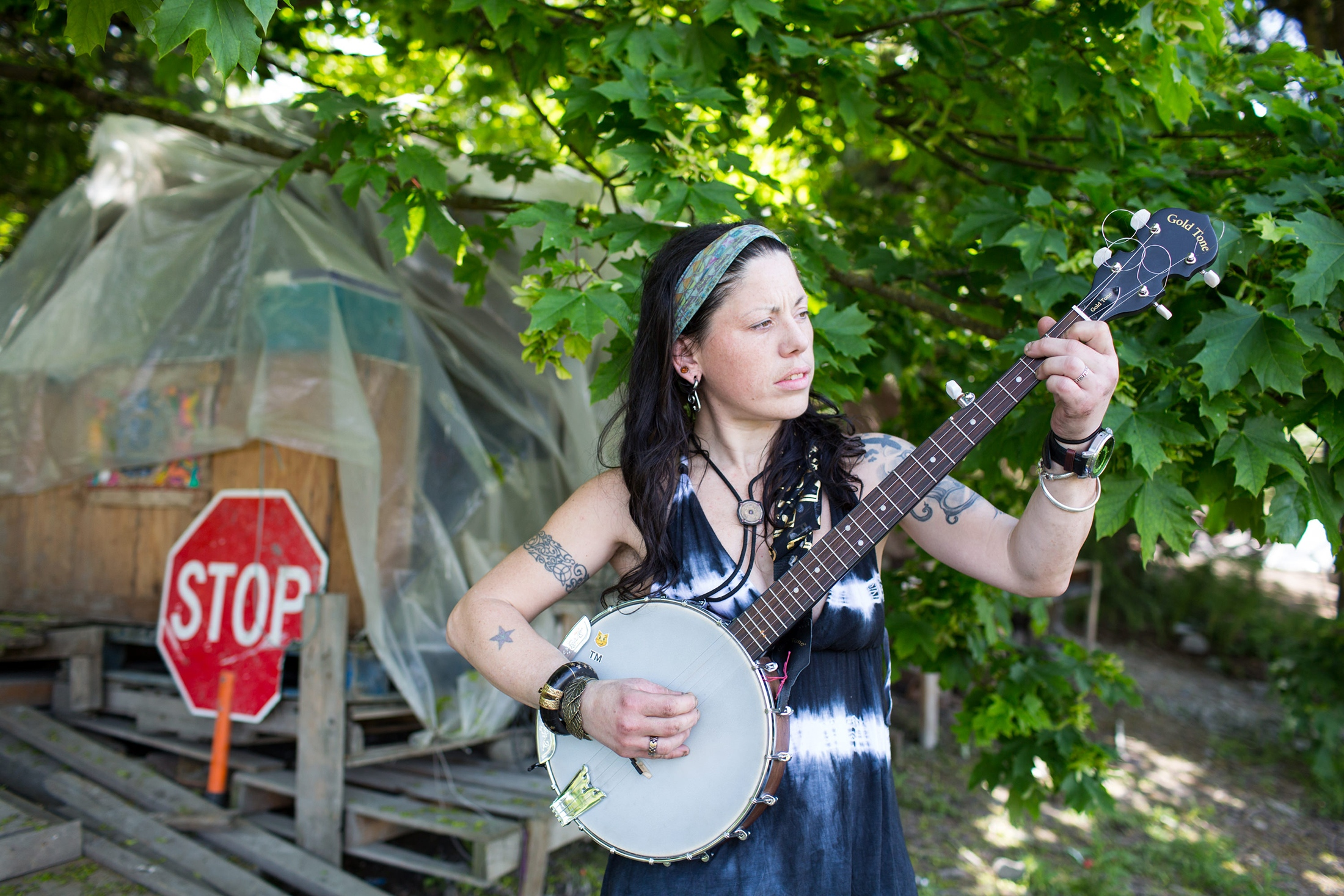 Paige Conca, 35, plays the banjo at her camp on the side of I-90 in Seattle, Washington. She has been homeless for four years.  'I cried all night': homeless women on their first night on the streets' for the Guardian