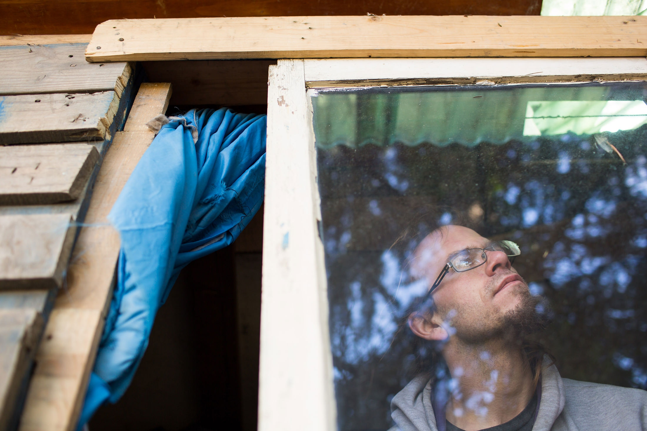 Chris Erickson, 32, inside the tiny home he built at the homeless encampment known as 'The Jungle' next to the onramp of I-90 in Seattle.  'This is the house that we built' for the Guardian