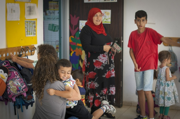 Kindergarden teacher Daisy Yaakov gets a hug from Bashar Abu Fane. Her co-teacher Layati Kaboha is in the background. Bridge Over the Valley, Hand in Hand School, Kafr Qara, Israel.