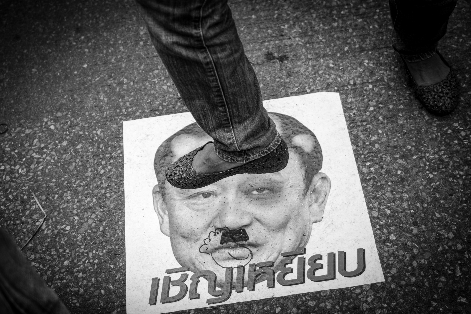 An image of exiled Prime Minister Thaksin Shinawatra is defaced and stomped on by his detractors in the streets of Bangkok.