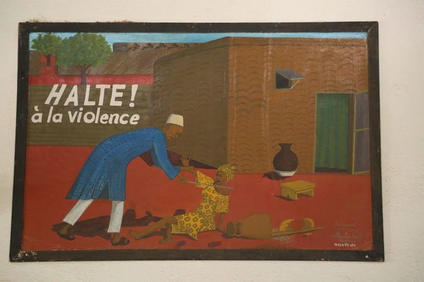A painting discouraging domestic violence, created by a young survivor, hangs near the entrance.