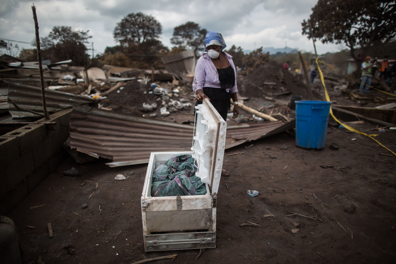 Photography image -  Eufemia García Ixpata observes a refrigerator with the remains that she believes are from her brother-in-law, found in one of the homes of her family, after the eruption of the Volcán de Fuego in San Miguel Los Lotes in Guatemala.