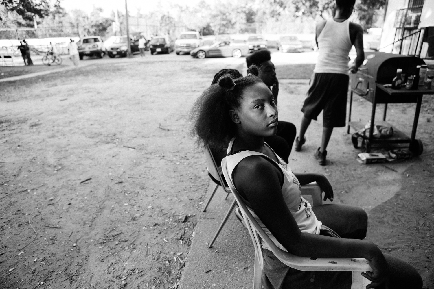 """Elizabeth gazes out of the fenced basketball court in Barry Farm on September 5, 2016. """"I want people to know the struggle we went through in this hood. We had no mon-ey. Let me tell you this song. We had no money, no jobs, no car, nothing."""" Elizabeth recalls holding a cardboard sign at the Gallery Place Metro Station with her family. In good times, they had enough money to rent a hotel room. In bad times, they had to sleep in a van on the streets. By 2013, Marshall's family found their way to Barry Farm Public Housing. """"That's when we started our new life,"""" says Elizabeth."""