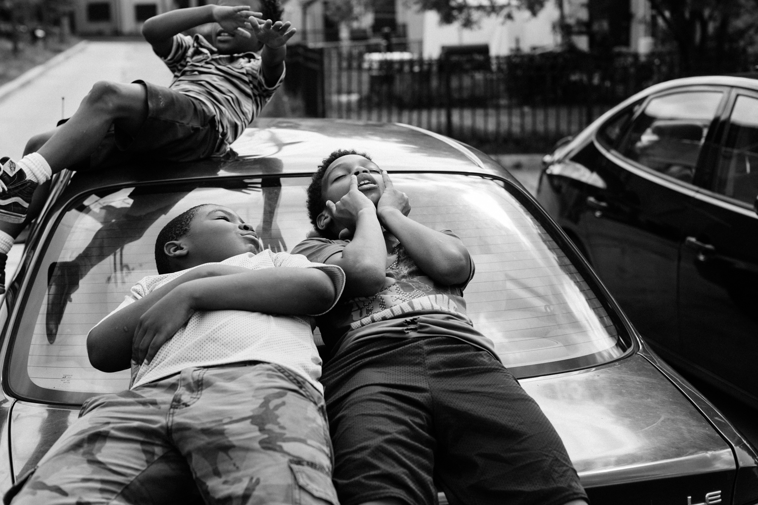 Dylan relaxes with his friends on top of his mother's car in Barry Farm on July 25, 2017.