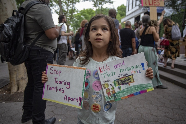 Tales from Trumpland, Angel, Age 6 holds up two signs she and her mother made to protest the Trump policy of separating children from their mothers and fathers at the Southwestern border and sending the children off detention camps.Manhattan. June 2o, 2018 (Kevin C Downs/Agence