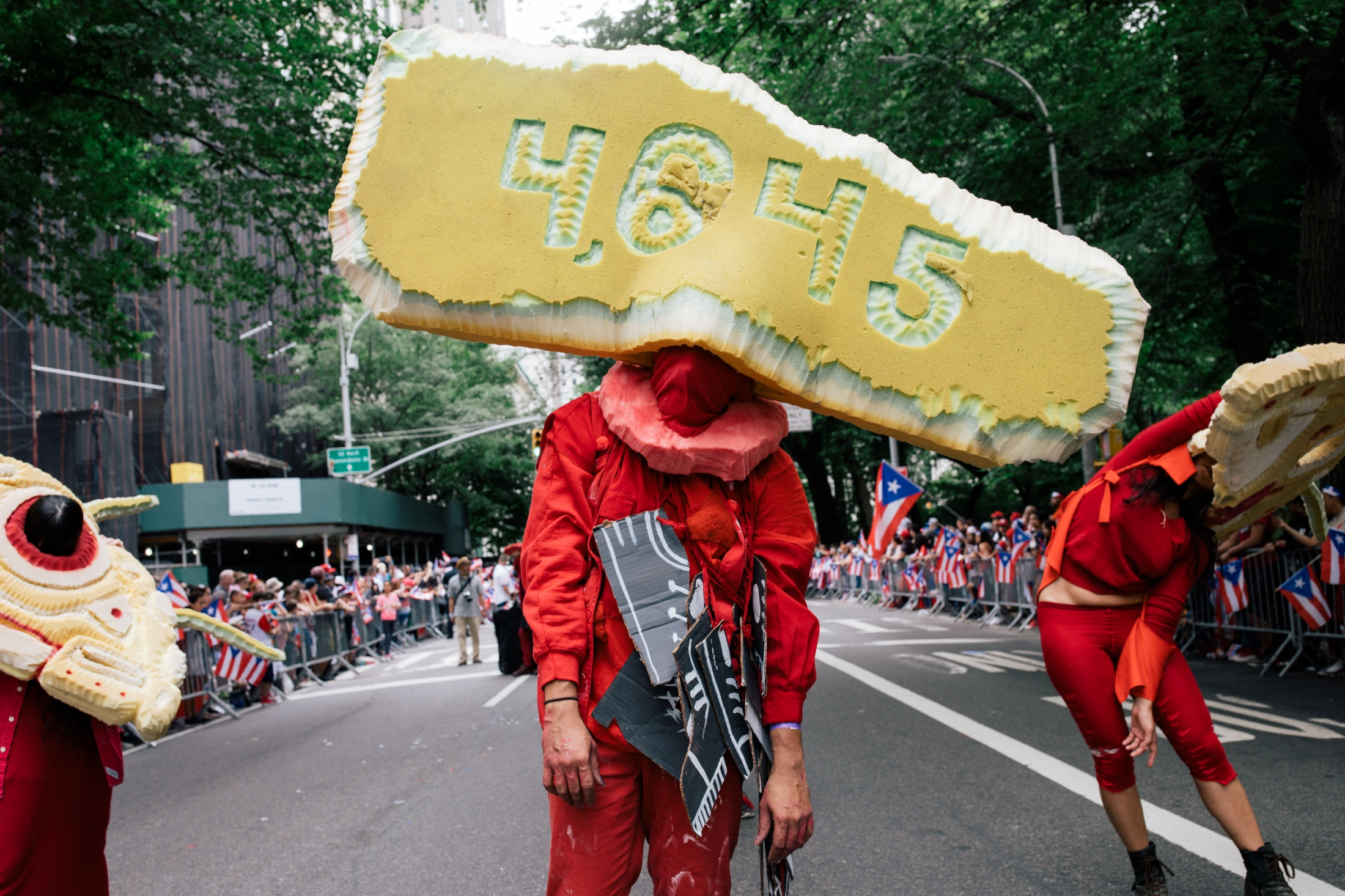 Puerto Rican performance art collective and sculptors Poncili Creación wear creations displaying the current estimated death toll from Hurricane Maria as the group dances down Fifth Avenue.