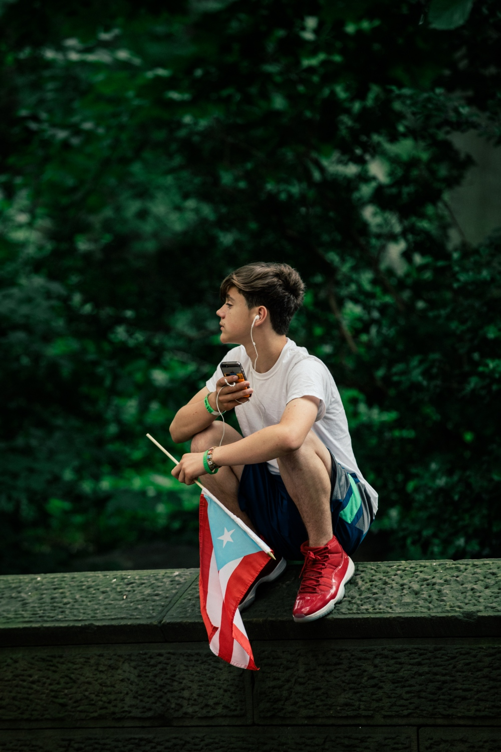 A young teen perches on the walls that surround Central Park to watch the parade.