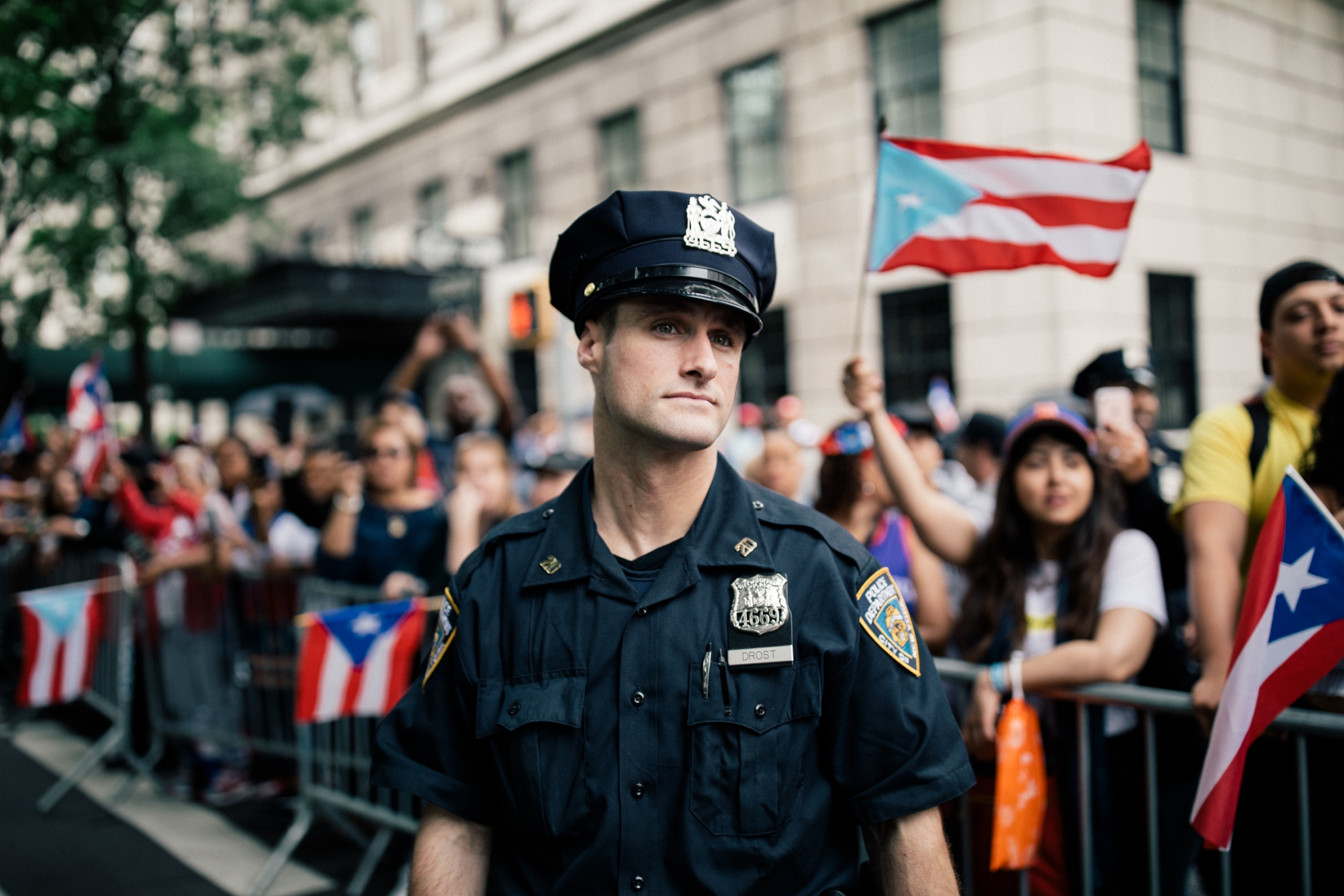 NYPD Officer Drost gazes down Fifth Avenue while Puerto Rican flags wave around him.