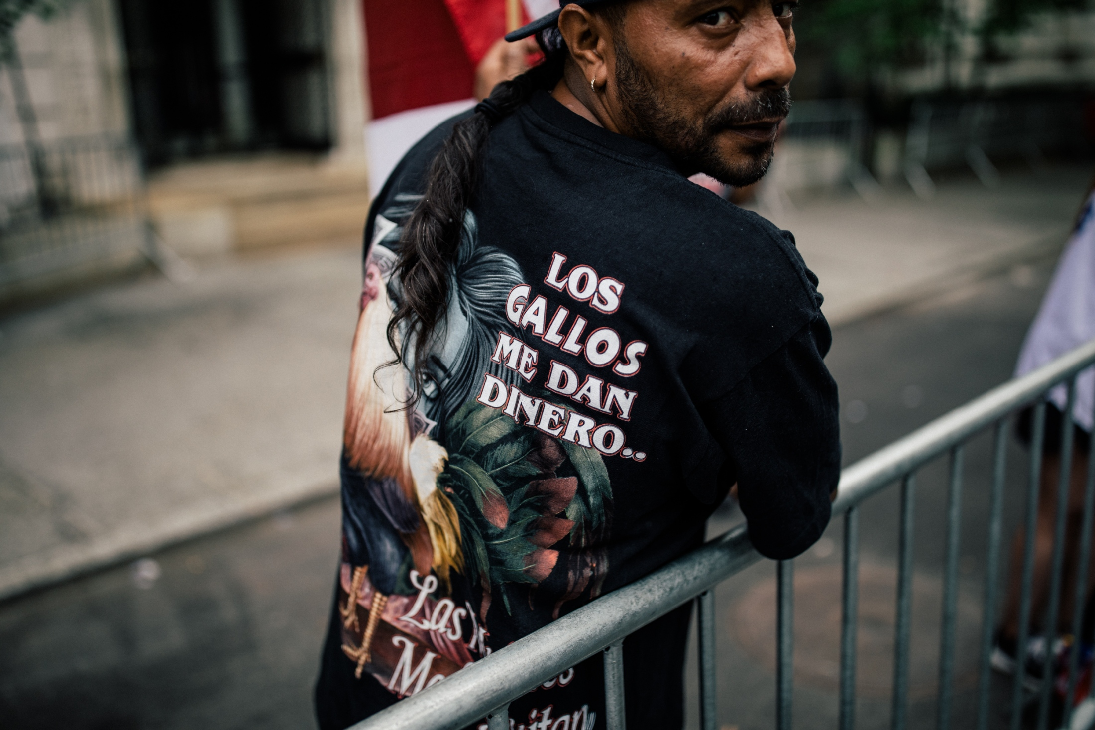 "A crowd member displays a shirt that translates as ""The roosters give me money,"" at Fifth Avenue and East 72nd Street."