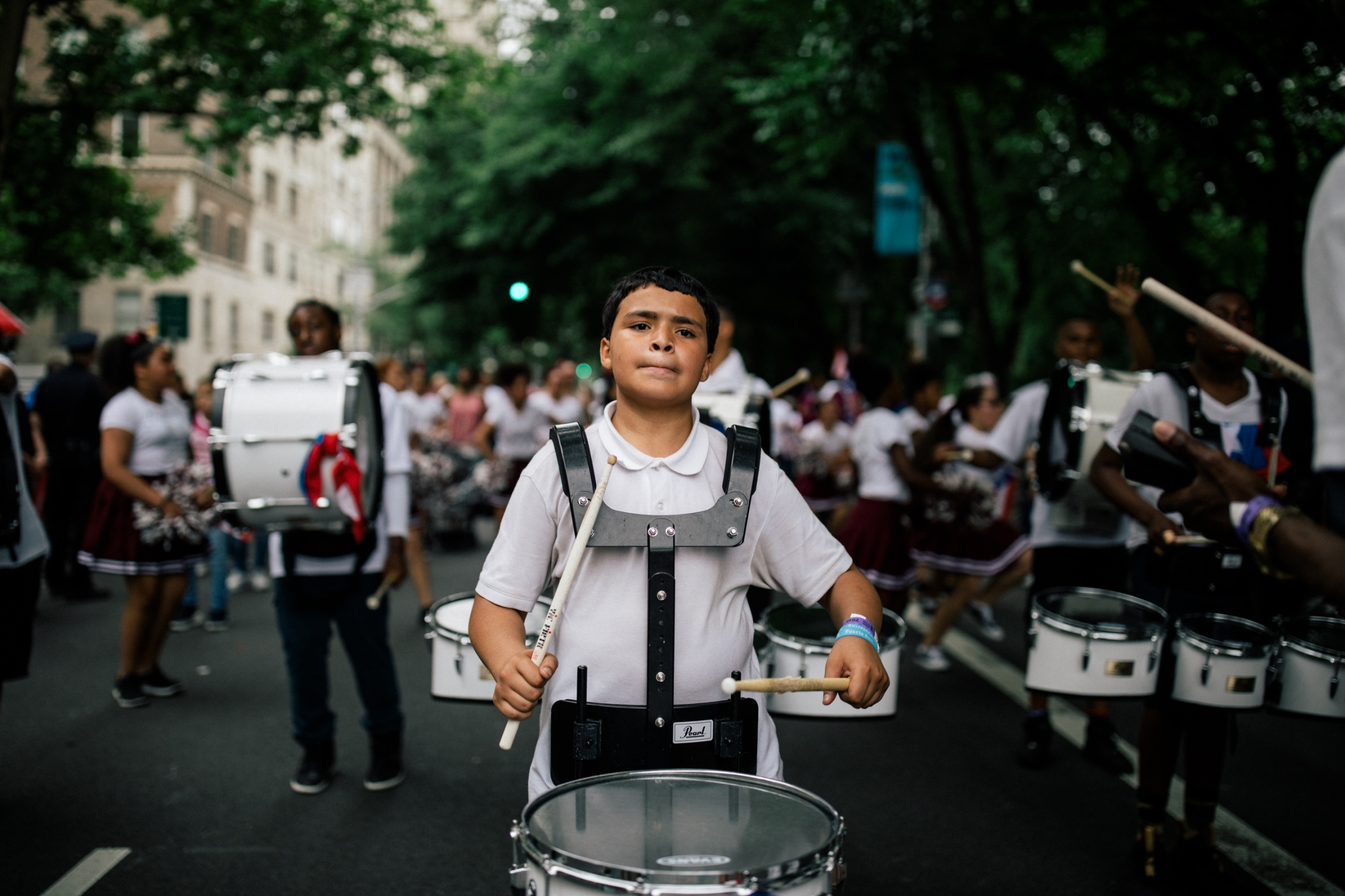 A young drummer plays the snare drum as he marches down Fifth Avenue.