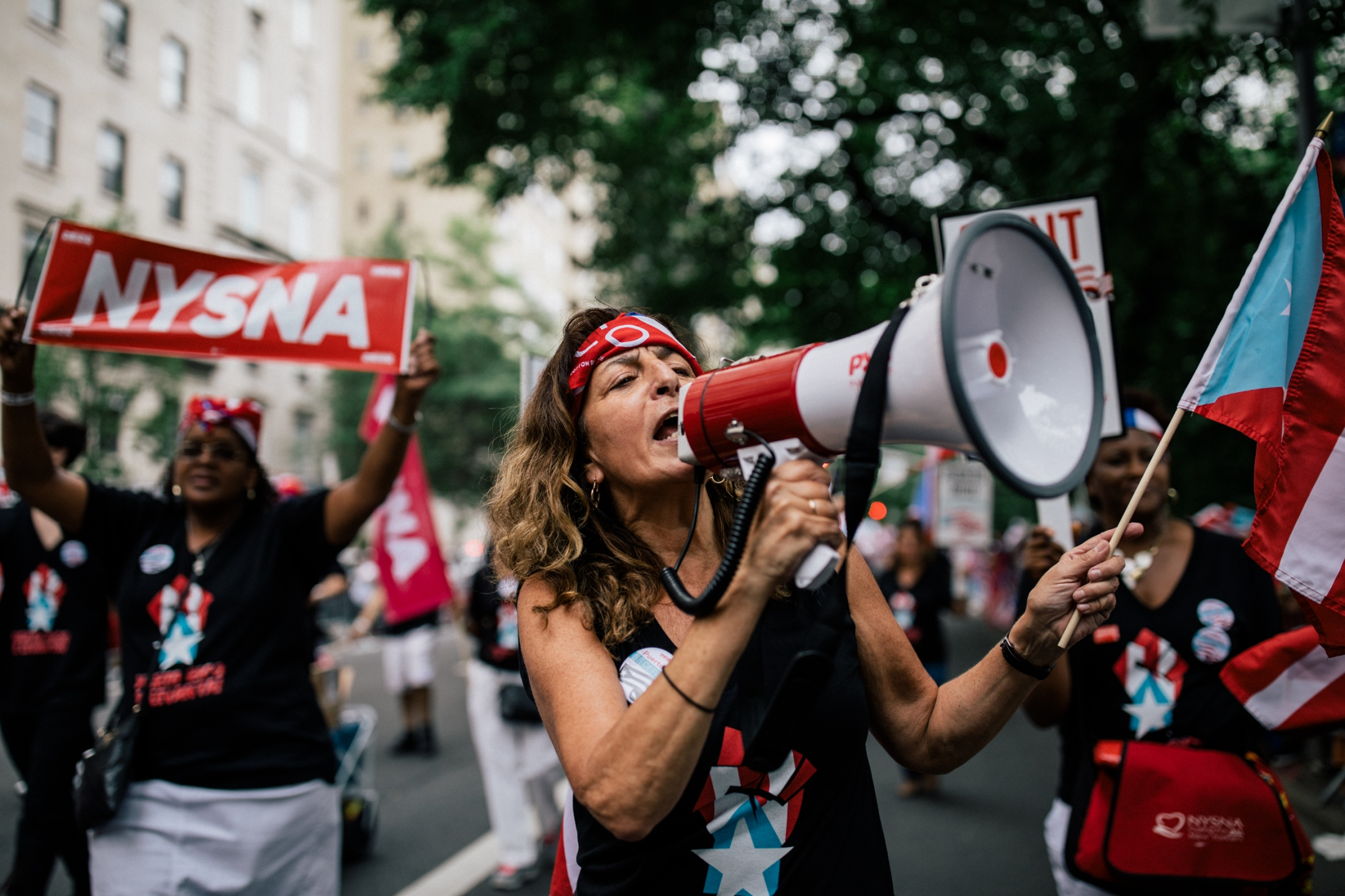 A member of New York State Nurses Association chants through a megaphone to the crowd on Fifth Avenue.