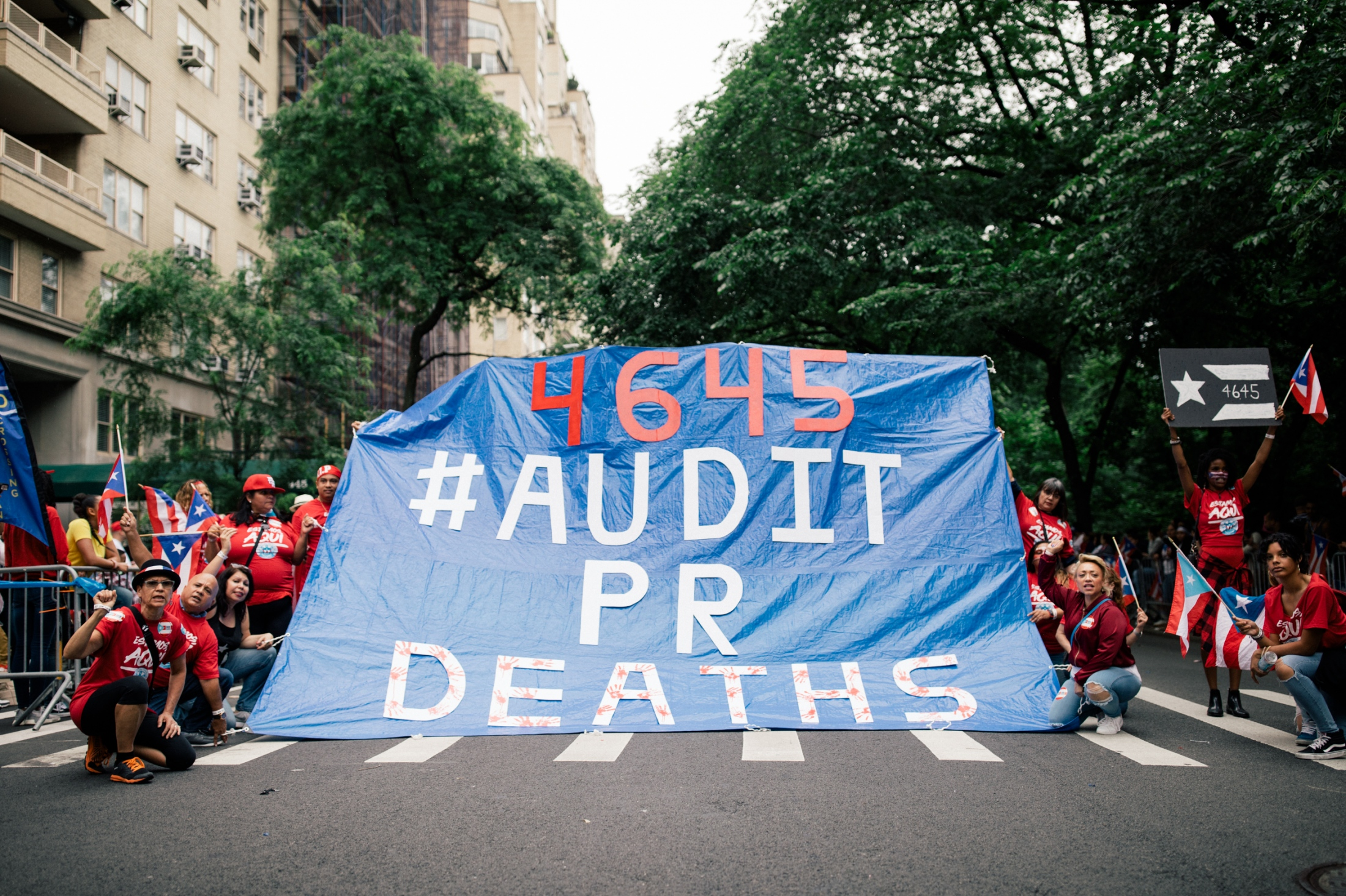 Marchers stop the parade briefly to hold open a large tarp displaying the midpoint of the newly released death toll estimates on Fifth Avenue and East 76th Street.