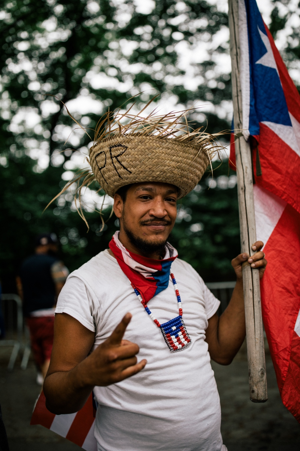 A member of the crowd holds a Puerto Rican flag and traditional Jibaro hat at Fifth Avenue and 76th Street.