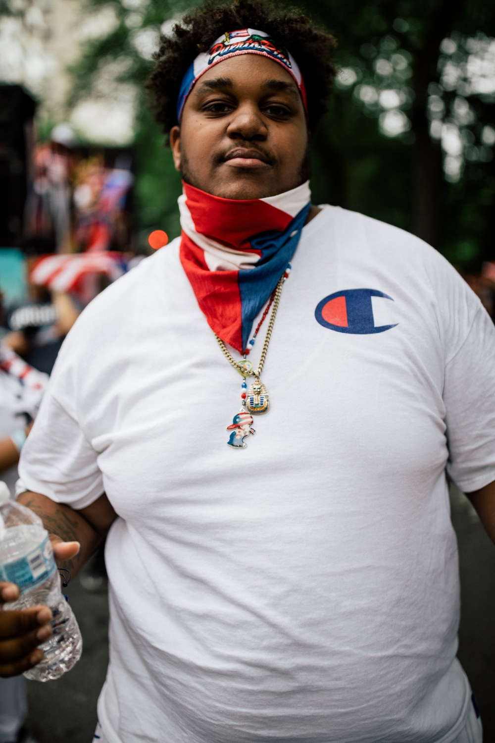 A marcher wearing a Puerto Rican flag bandana and sporting Puerto Rican–themed necklaces, at Fifth Avenue and 76th Street