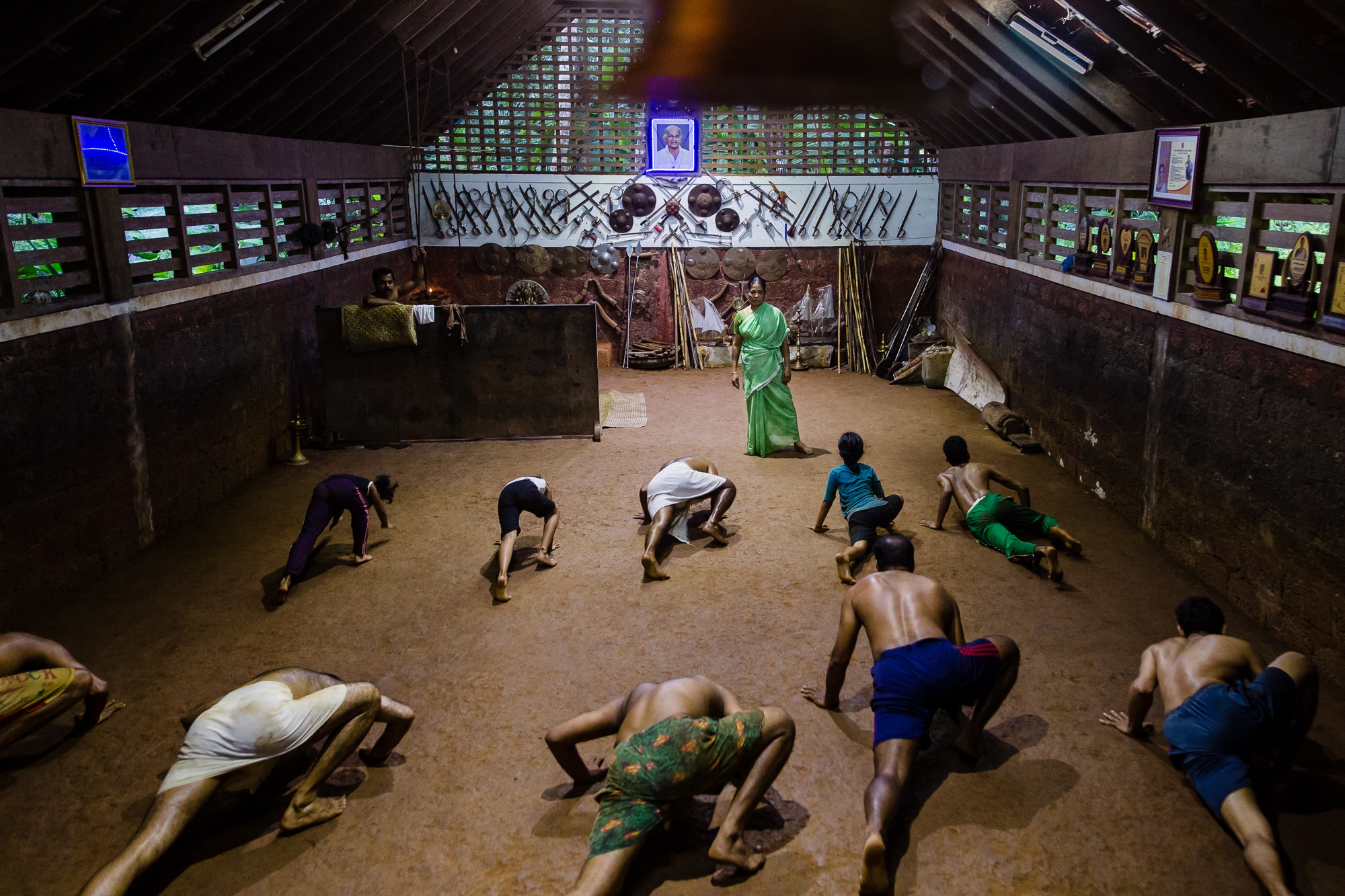 Vatakara, Kerala, INDIA - September 18, 2017: Meenakshi Gurukkhal, 76, watches on as students practice Kalaripayattu techniques. Commonly all 'Kalaripayattu' grand masters are male. Meenakshi is an exception, being a female grand master that men respect and look up to.