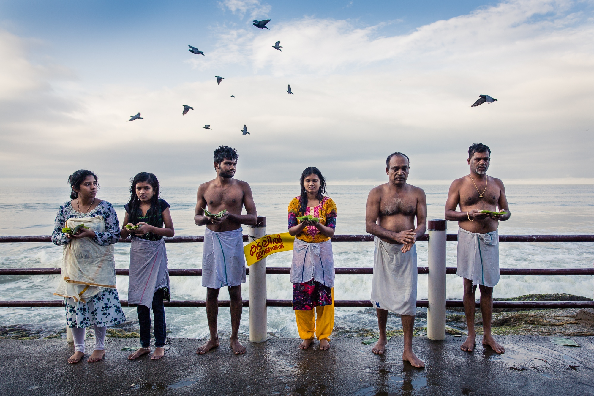 Nandi, Kerala, INDIA - September 12, 2017: Meenakshi's grandchildren (FL) Ninu, 32, Lena, 14, Milind, 21, Jaimi, 23, and her sons Sajeev, 53, and Pradeep, 52, perform the Hindu Śrāddha ritual in honor of Meenakshi's late husband, Raghavan. (Tradition forbids the wife to attend to this ritual). Raghavan was Meenakshi's martial arts master. When he passed away in 2010, she took over his legacy. The entire family continues to practise Kalaripayattu in the temple that Raghavan had built.